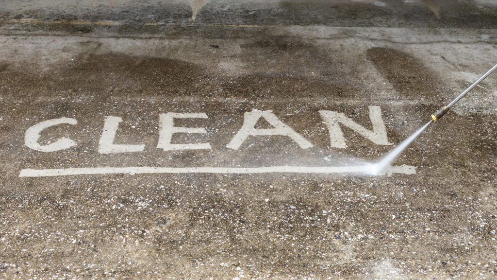 The word Clean spelled out by pressure washing on patio floor.