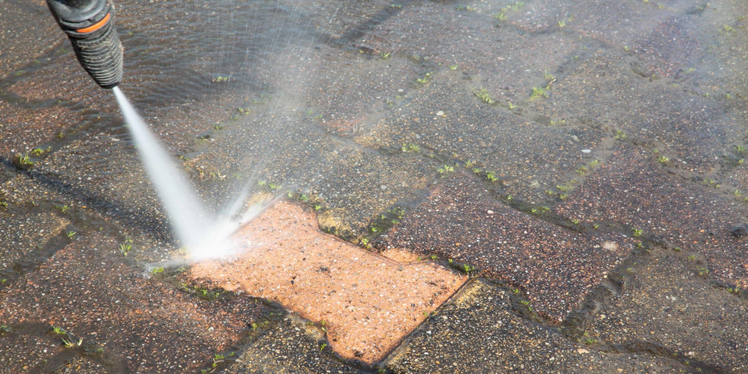 Pressure washing a brick patio floor.