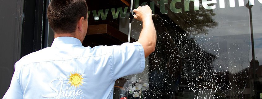 Shine window washer cleaning a commercial storefront business window.